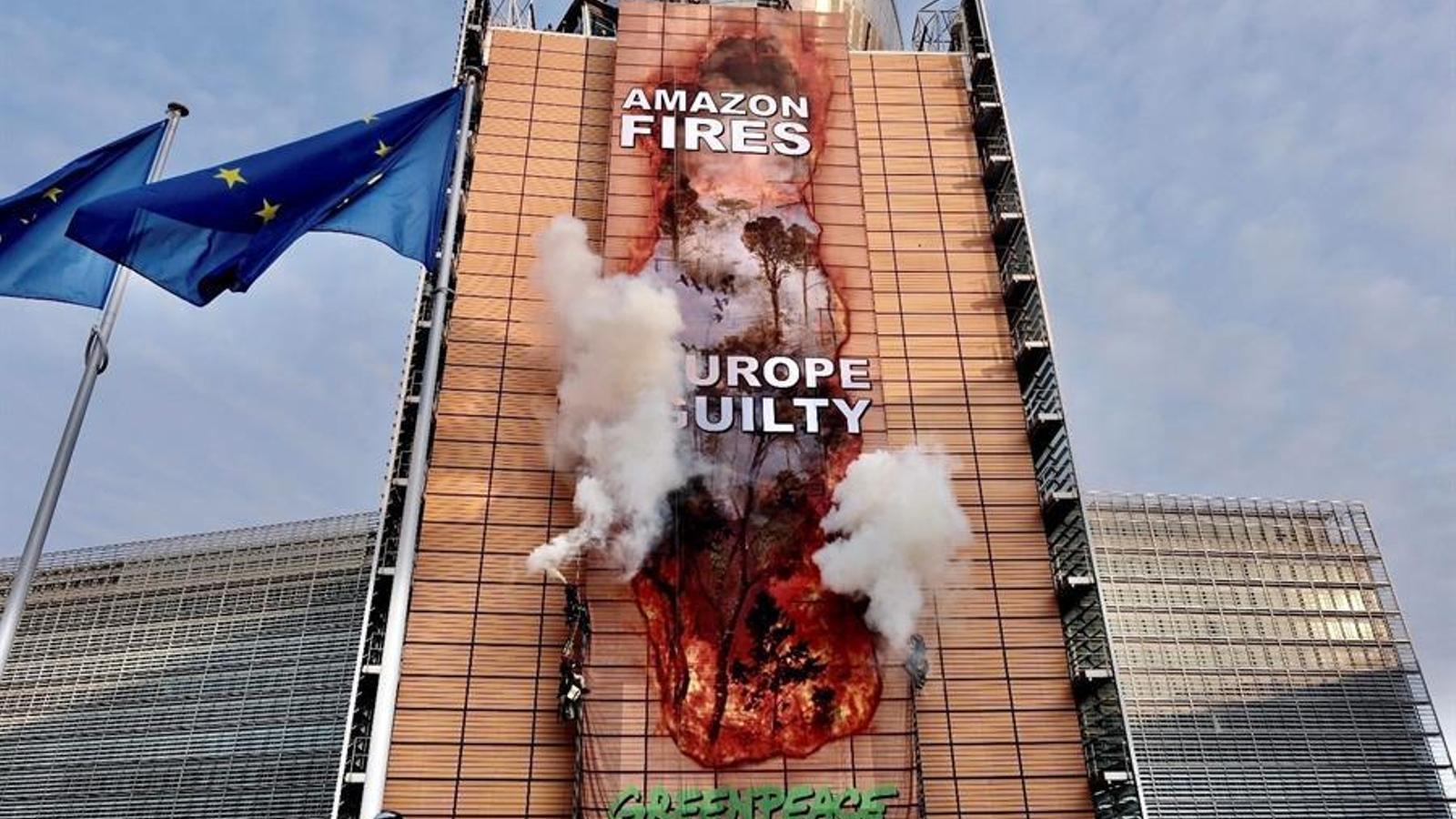 Activistes de Greenpeace han penjat un enorme mural a la façana de la seu de la Comissió Europea per denunciar la crema de l'Amazònia