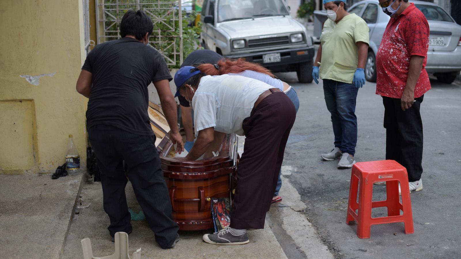 Familiars d'una víctima de Covid-19 acomoden la difunta al fèretre a Guayaquil, Equador
