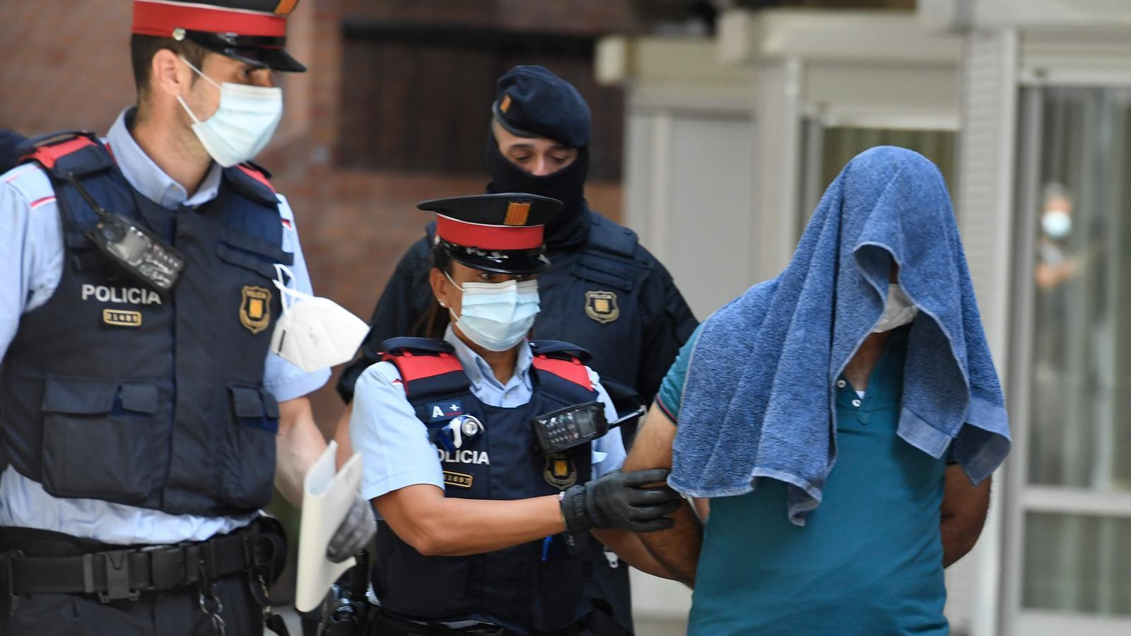 Agents dels Mossos amb un dels dos detinguts en l'operació d'aquest matí a la Barceloneta