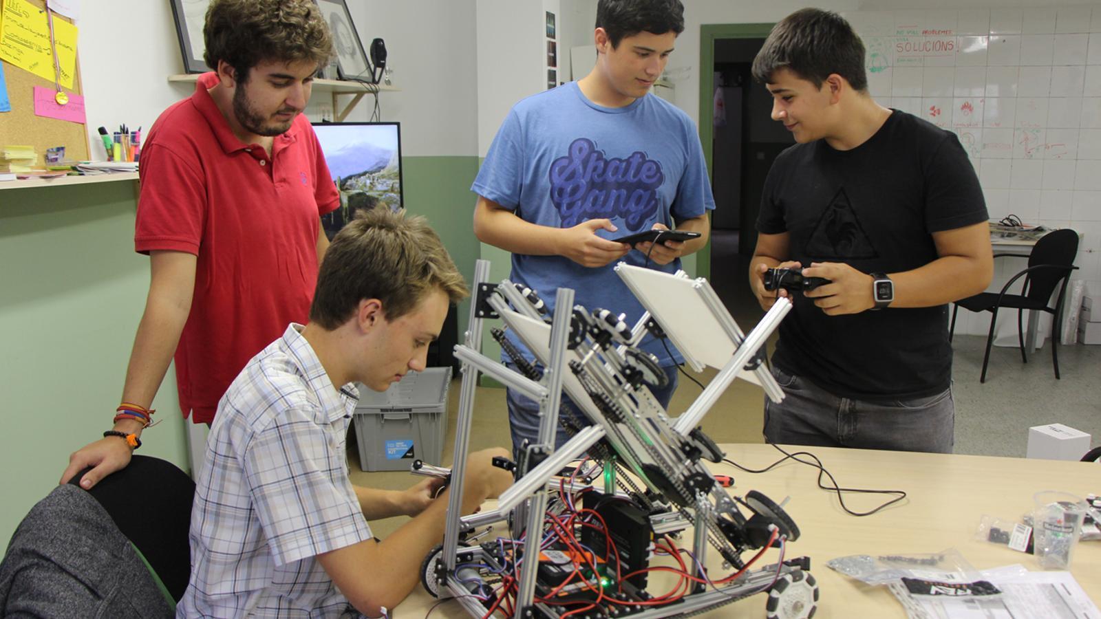 Els tres joves de l'equip andorrà i el seu monitor treballant en la preparació del robot. / L. M.