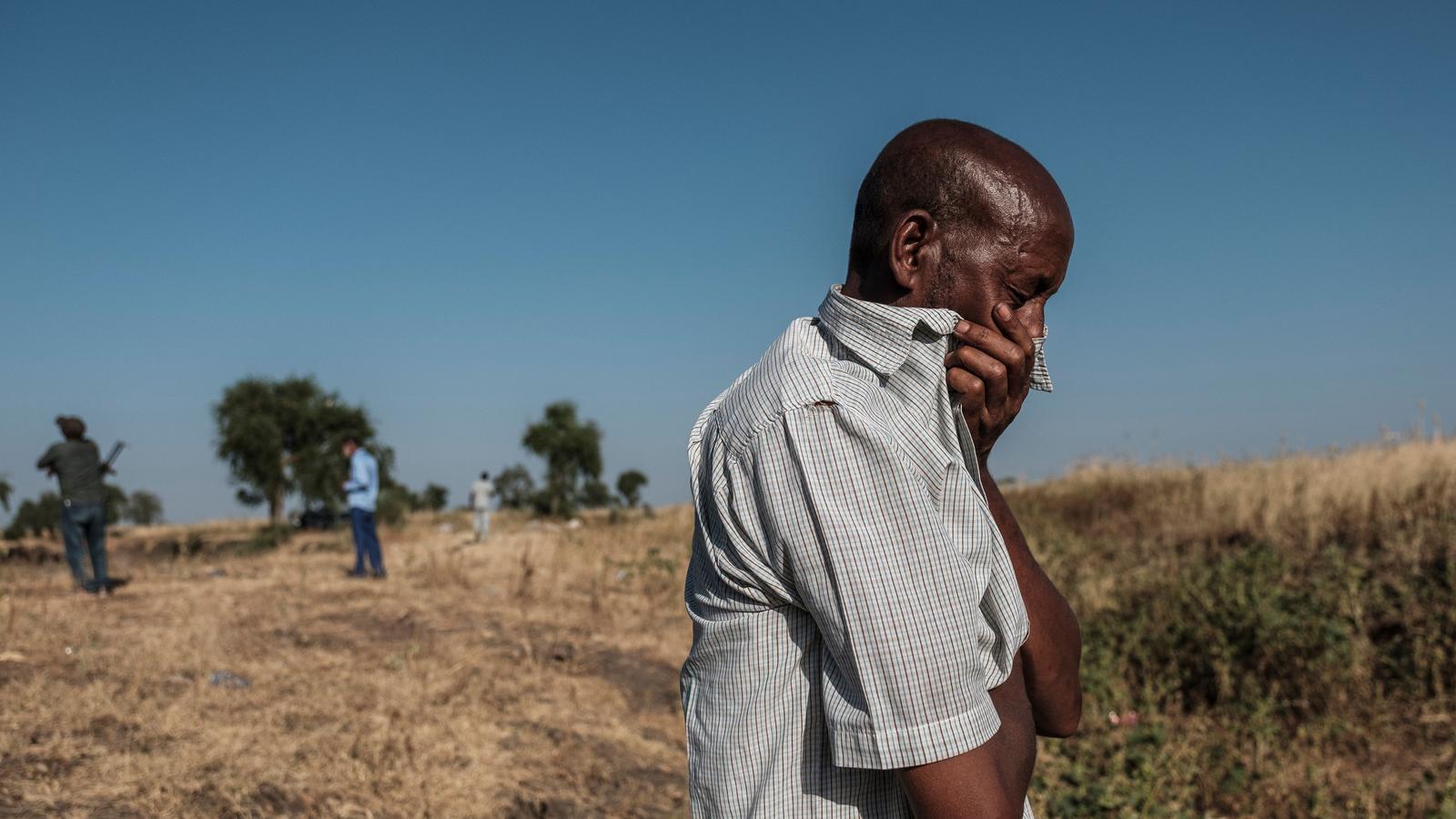 Un home reaccionant mentre esta a a prop d'una rasa als afores de Mai Kadra, Etiòpia