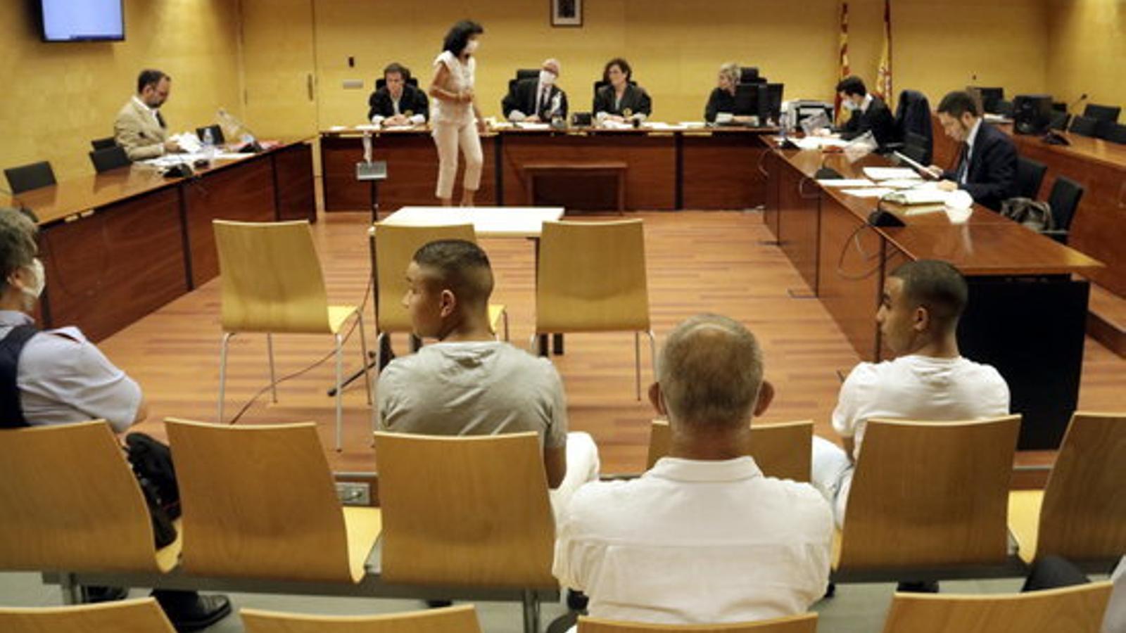 Els dos joves acusats, d'esquenes, abans de començar el primer judici pels aldarulls en les protestes després de la sentència del Procés a l'Audiència de Girona / MARINA LÓPEZ (ACN)