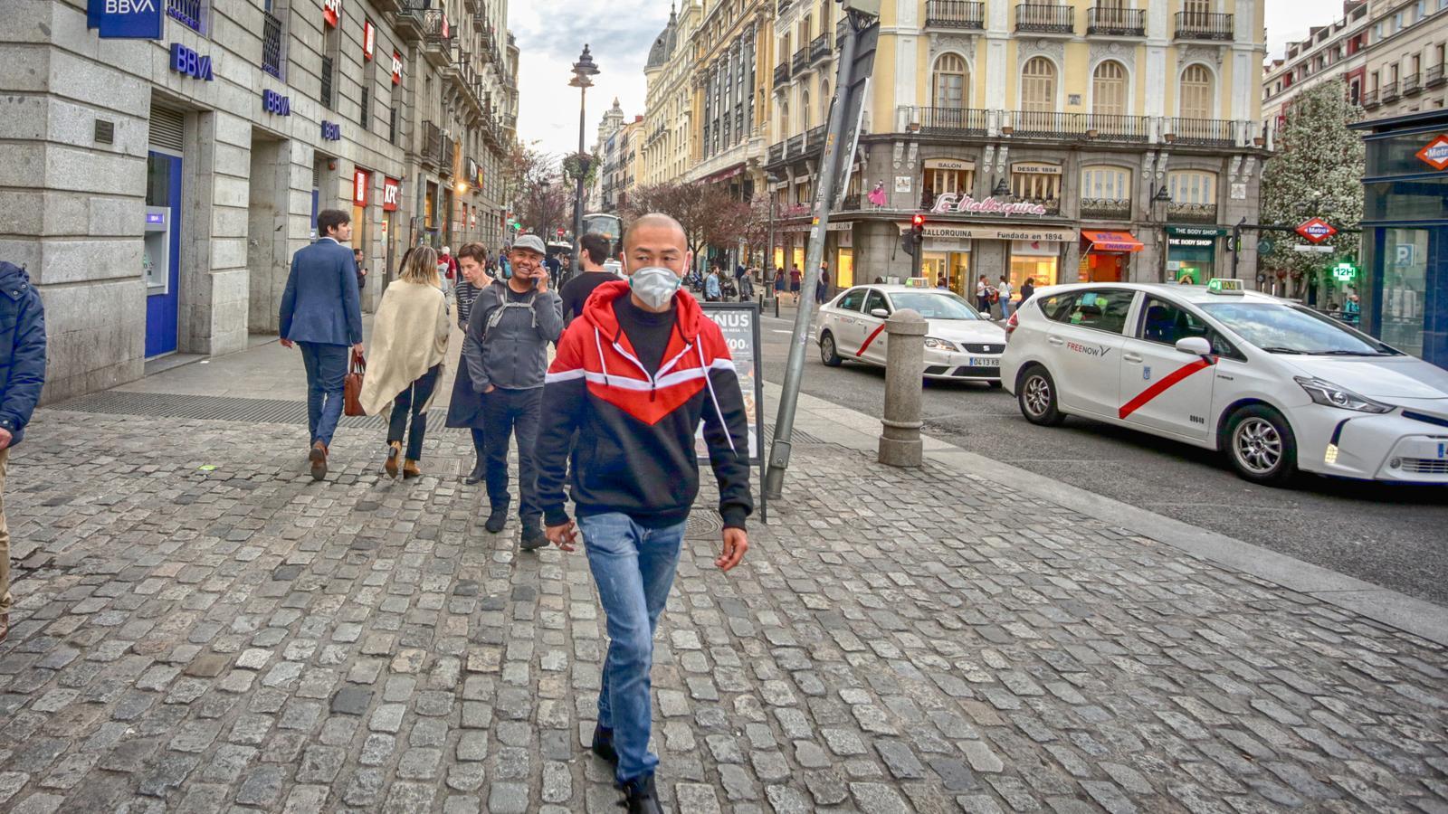 Un home passejant amb mascareta pel centre de Madrid.