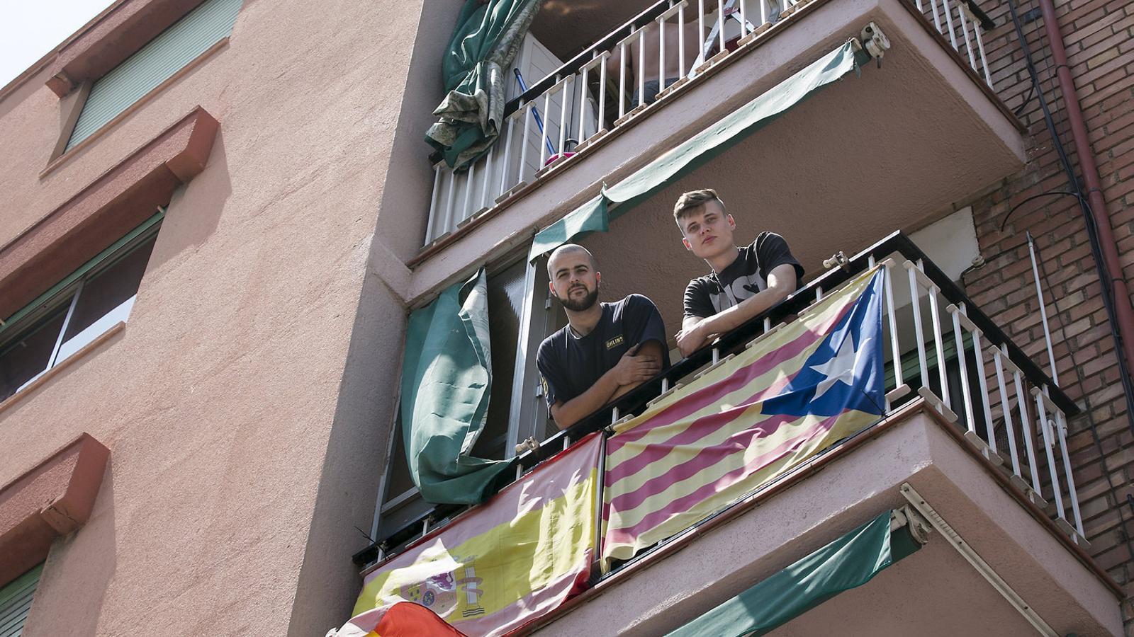 Els companys de pis Èrik i David al balcó de Badalona on tenen penjada una estelada i una bandera espanyola. / CRISTINA CALDERER