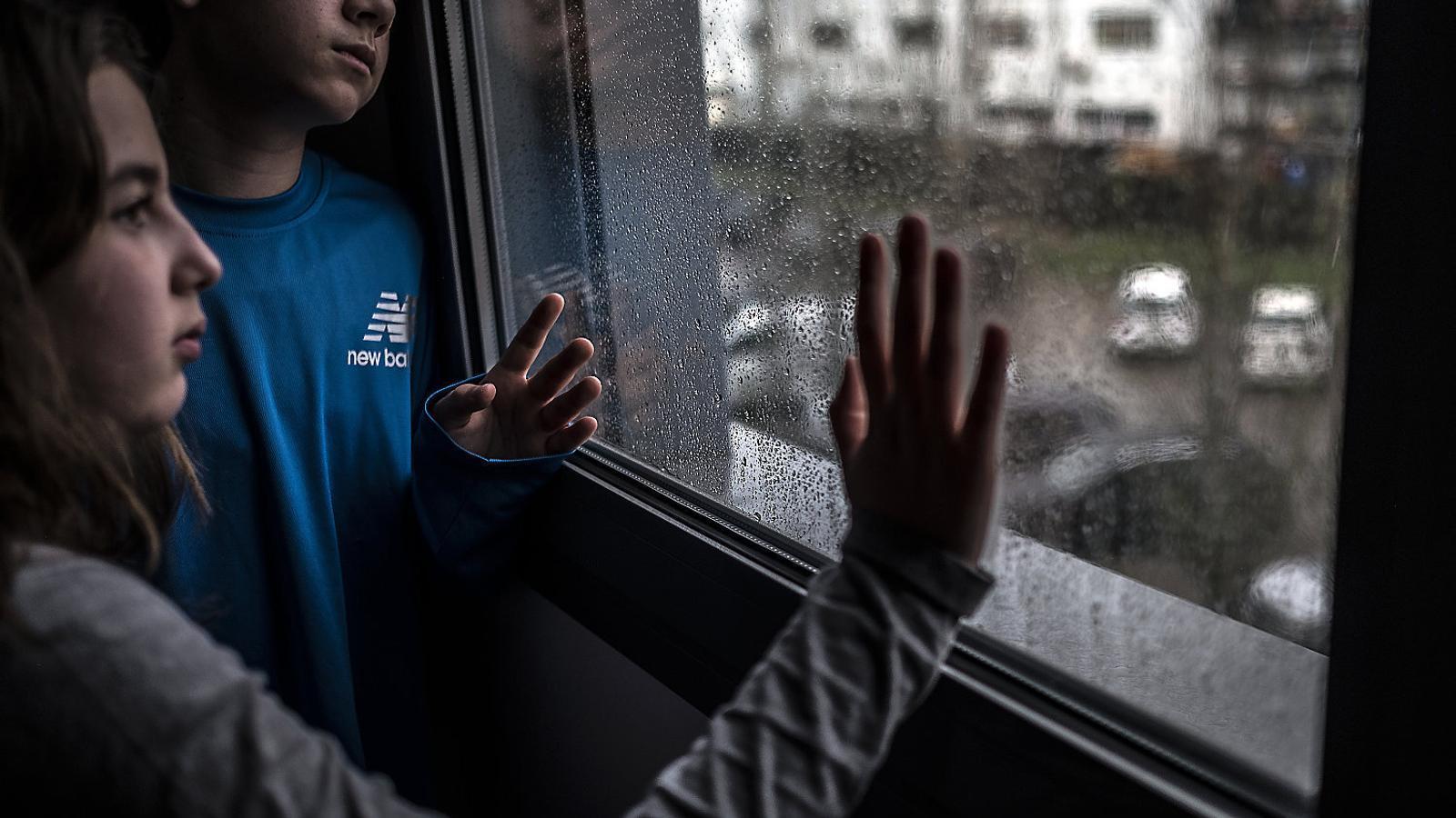 Dos infants observant la pluja des de la finestra de casa, en una de les moltes jornades de confinament des que es va decretar l'estat d'alarma, el 14 de març.
