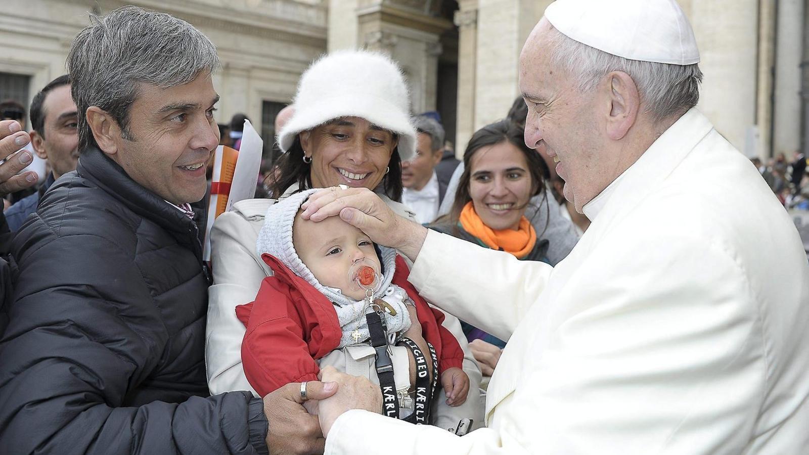 El papa Francesc saludant una família en una audiència general a la Ciutat del Vaticà el 23 de març.