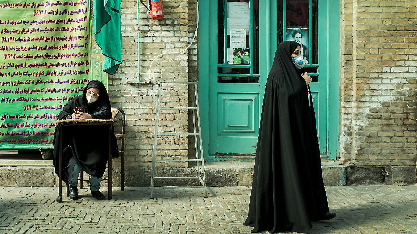 Dues dones es protegeixen amb mascaretes al mig del carrer a Teheran.