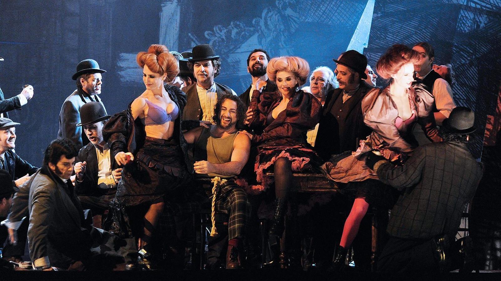 El tenor John Osborn, amb samarreta sense mànigues, a l'escenari del Liceu envoltat de part del repartiment de l'òpera Benvenuto Cellini.