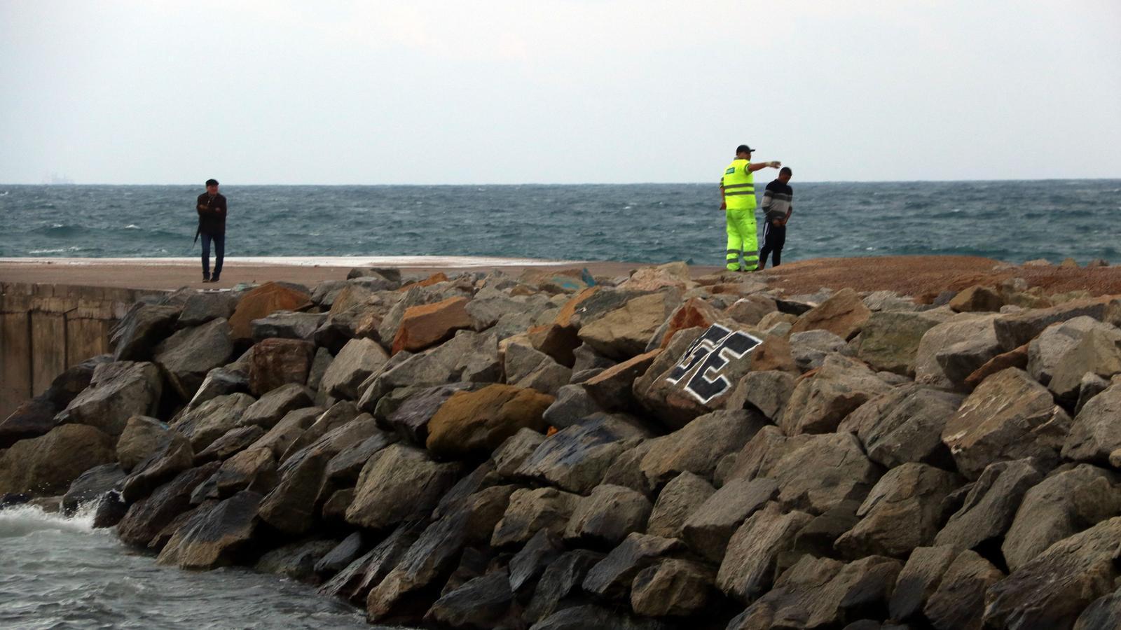 Un espigó de Barcelona amb un operari fent fora dos joves que miraven el mar, el 14 d'octubre de 2018