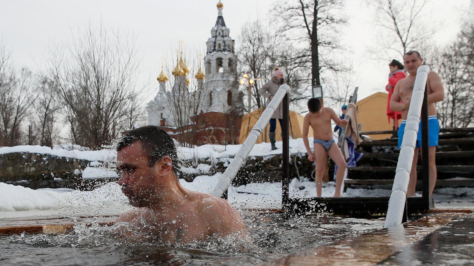 Un home banyant-se en una piscina d'aigua gelada a Moscou, malgrat que les temperatures són sota zero.