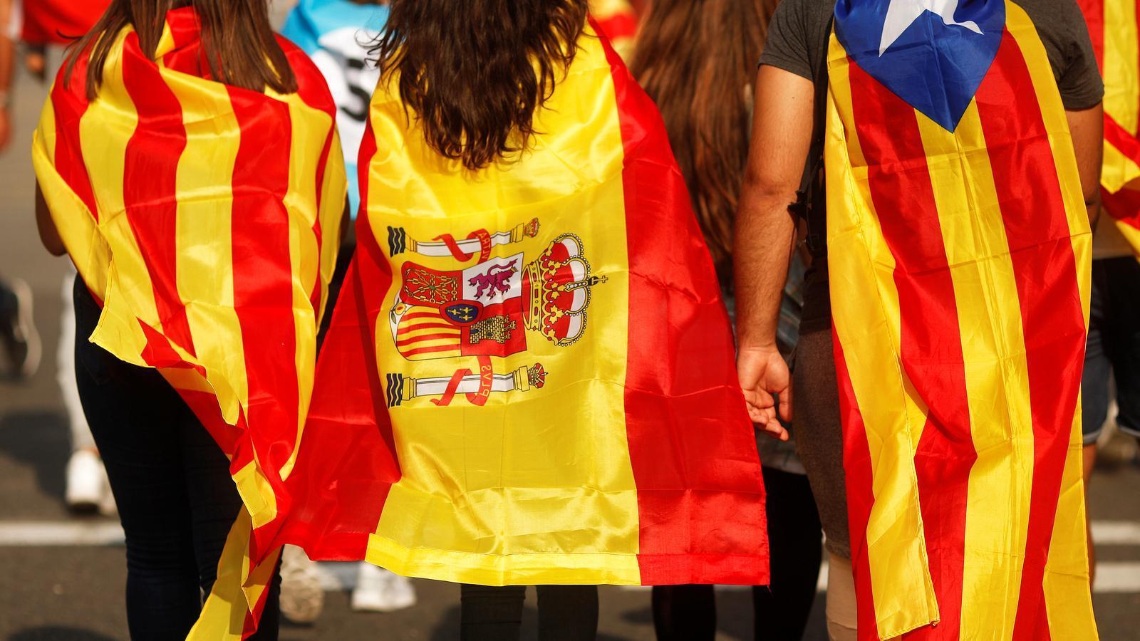 Tres joves vestits amb la bandera catalana, espanyola i l'estelada, a la manifestació contra la violència policial, el passat 3 d'octubre. / JON NAZCA / REUTERS