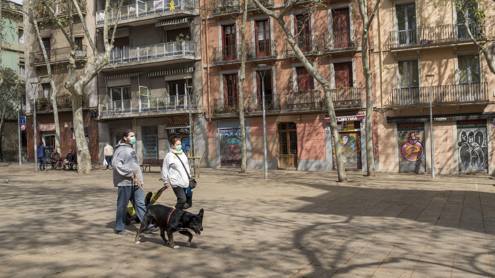 Dues persones passejant el gos a la plaça de la Virreina de Barcelona, amb els comerços tancats