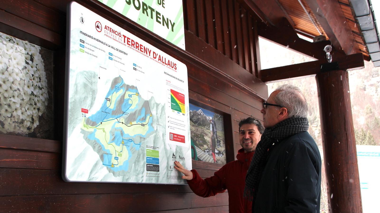 El cap d'àrea de Medi Físic del Cenma, Marc Pons, i el ministre de Turisme, Francesc Camp, consulten un dels panells. / C.G. (ANA)