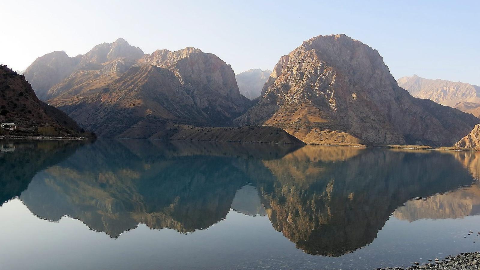 Les muntanyes es reflecteixen sobre l'aigua encalmada del llac Iskanderkul, on diuen que va morir Bucèfal, el cavall d'Alexandre el Gran.