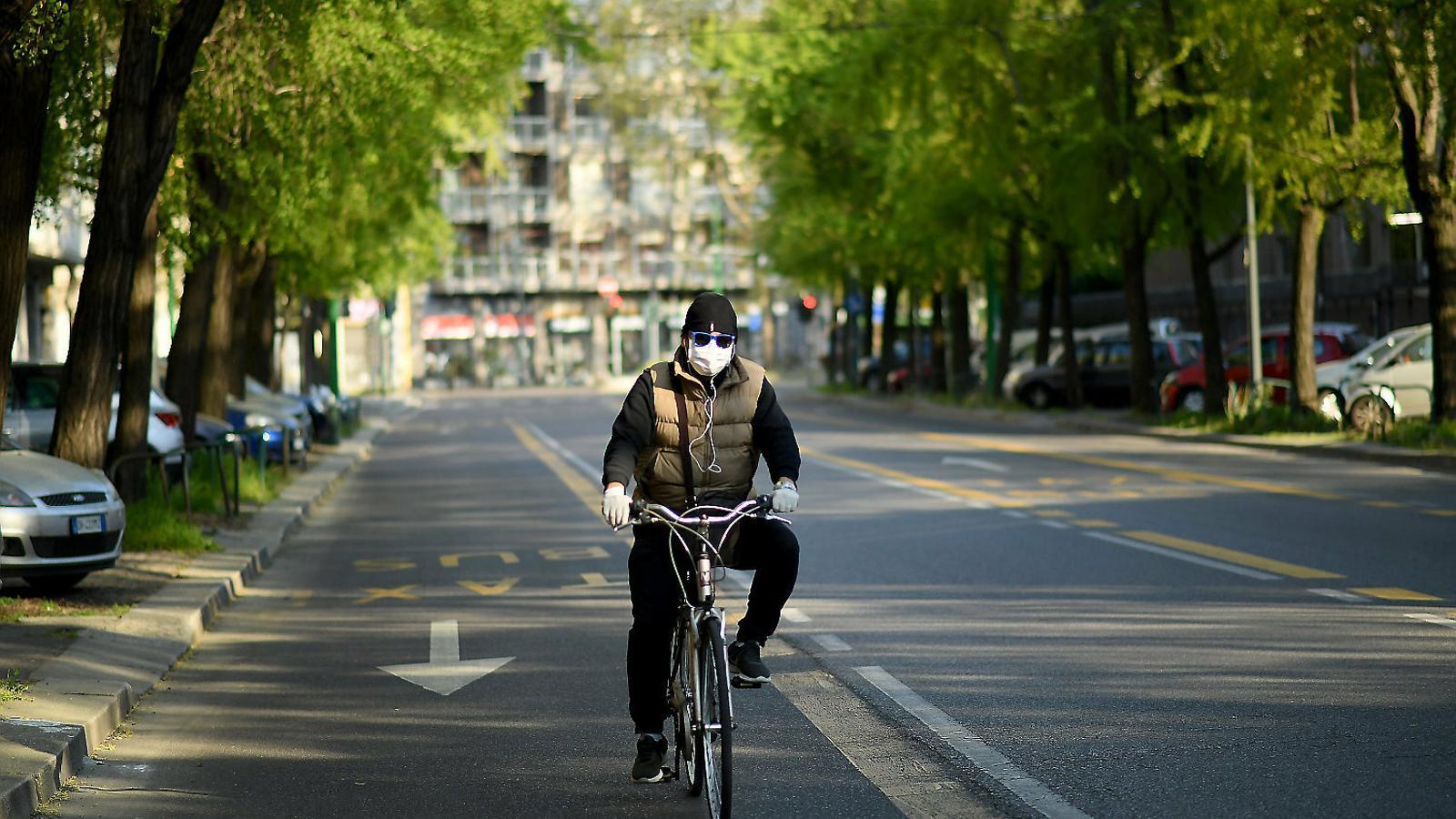 Un home en bici pels carrers de Milà sense cotxes ni contaminació.