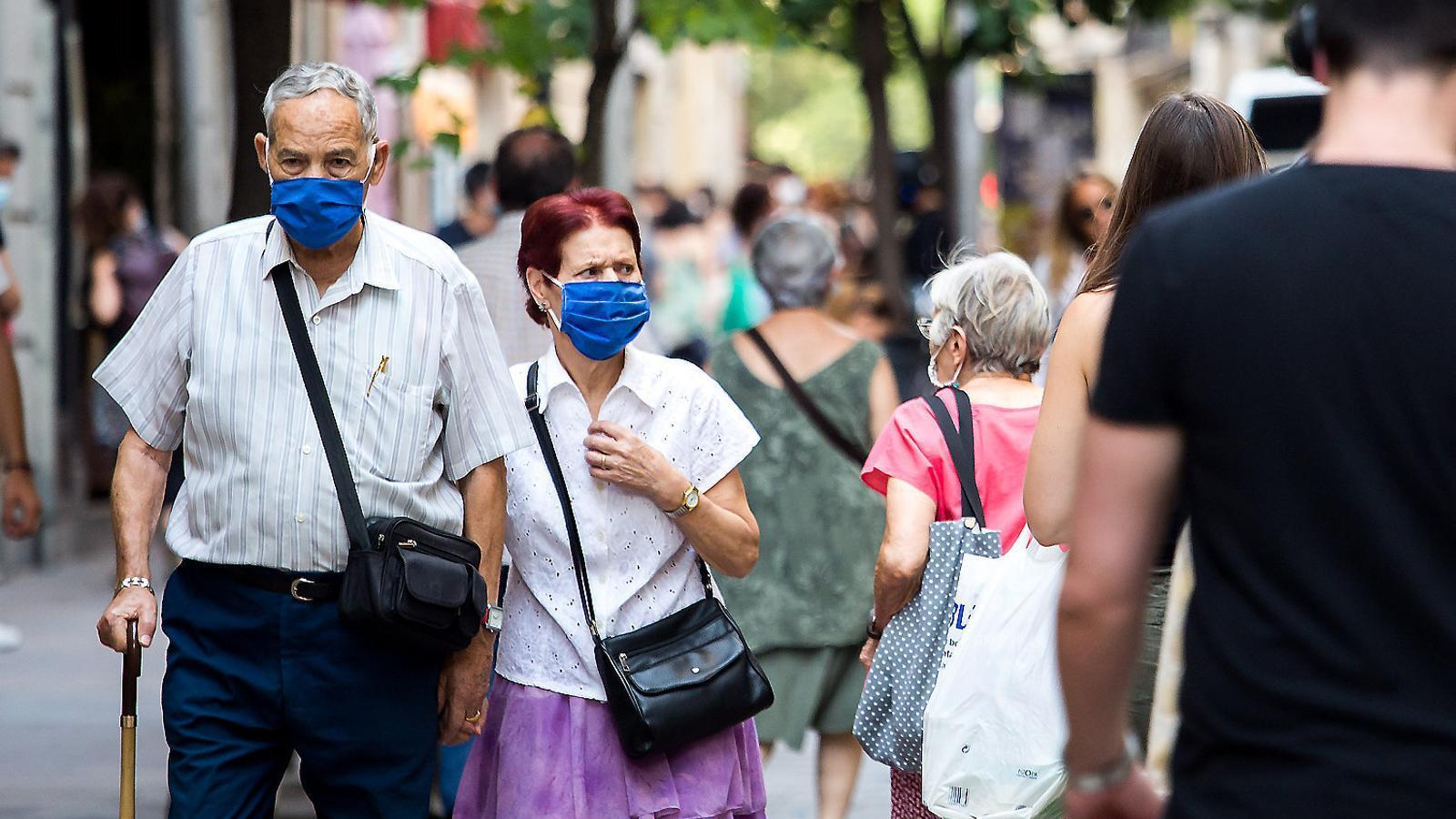 Diverses persones amb mascareta, passejant pel carrer