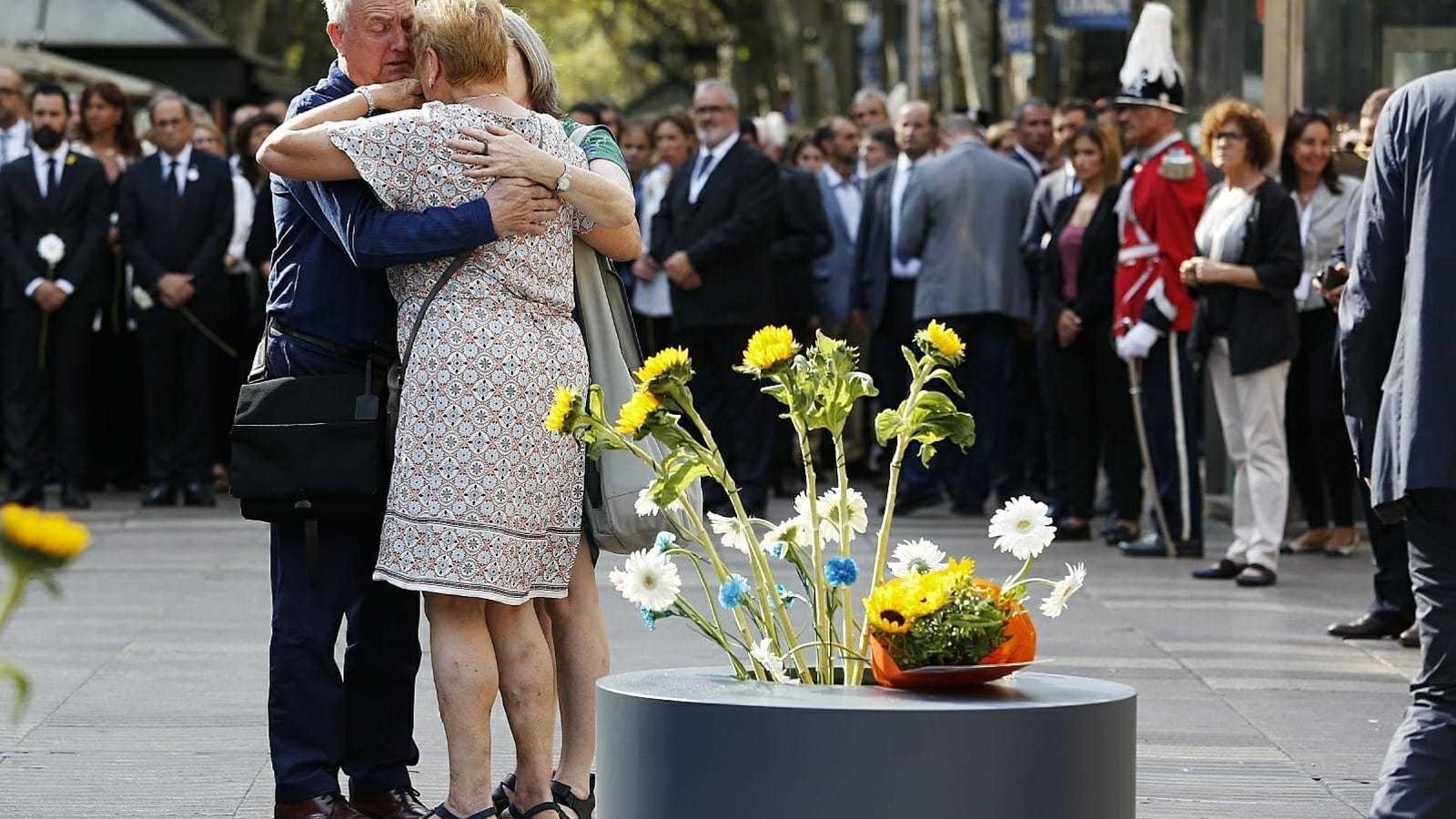 Familiars de les víctimes s'abracen davant del mosaic de Miró, després de fer l'ofrena floral