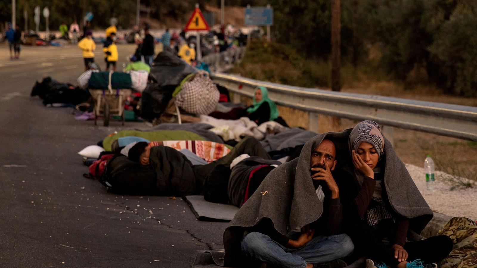 Una parella resident de Mória, asseguda al voral de la carretera després d'haver-ho perdut tot
