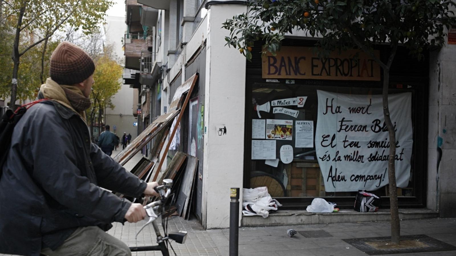 Una desena d'activistes han tret les planxes metàl·liques que tapiaven el local amb una serra radial. / CÈLIA ATSET
