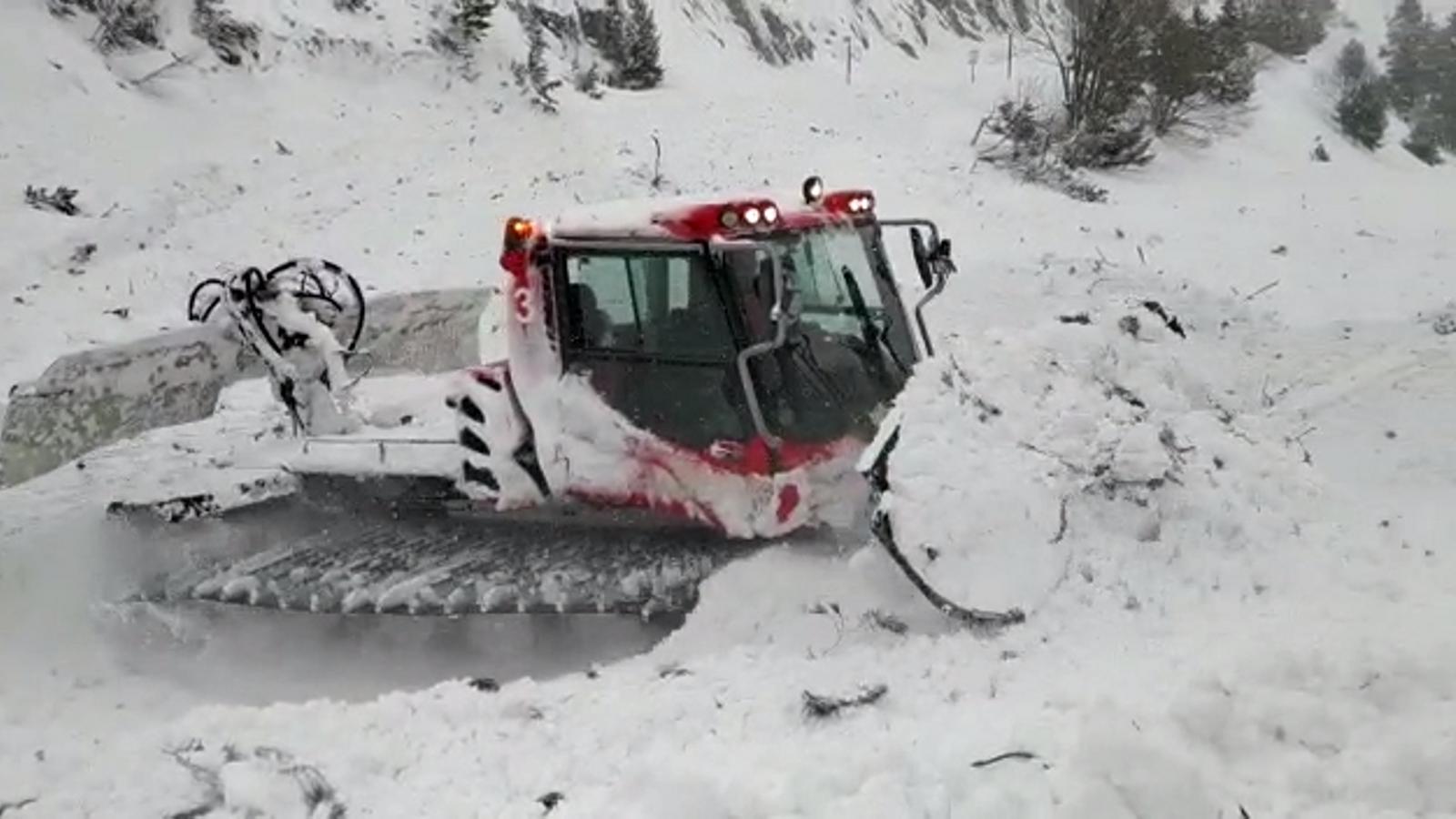 Les màquines llevaneus retiren la neu de la carretera després de l'allau provocat.