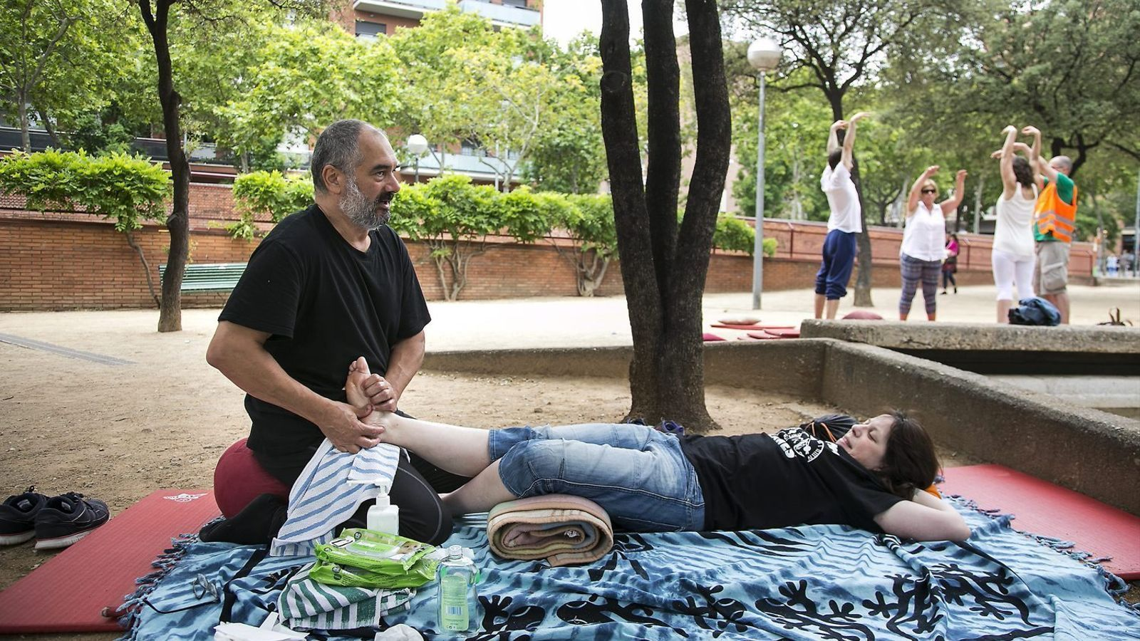 Un usuari del Banc del Temps de Barcelona ofereix massatges a la resta d'usuaris ahir a la Plaça Sóller.