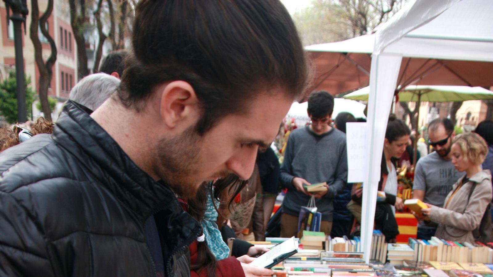 Un noi mira llibres a la Rambla Nova de Tarragona.