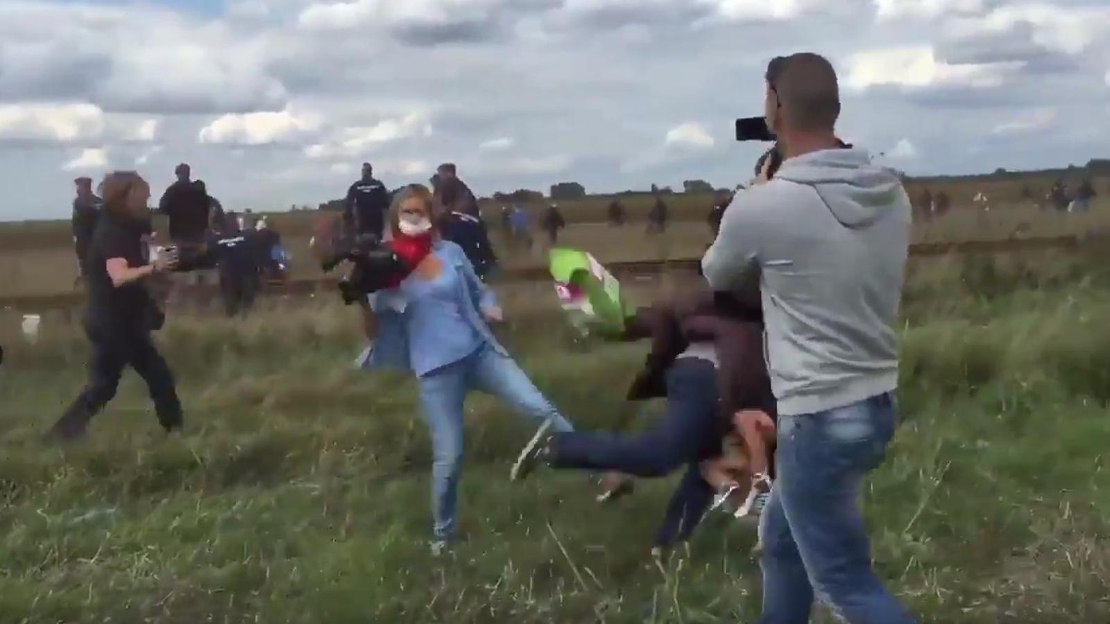 Una reportera de la TV hongaresa fa la traveta a un refugiat sirià que fugia de la policia