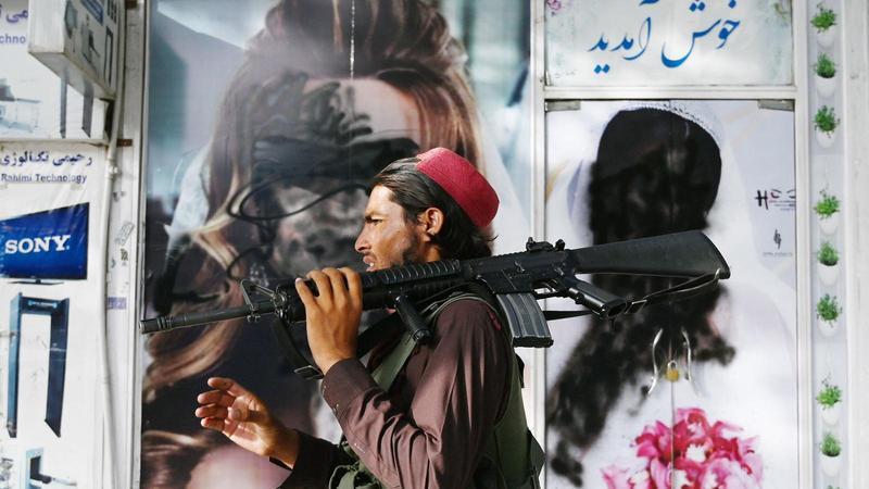 Un combatent talibà passa per davant d'un saló de bellesa amb imatges de dones pintades amb un aerosol a Shar-e-Naw a Kabul