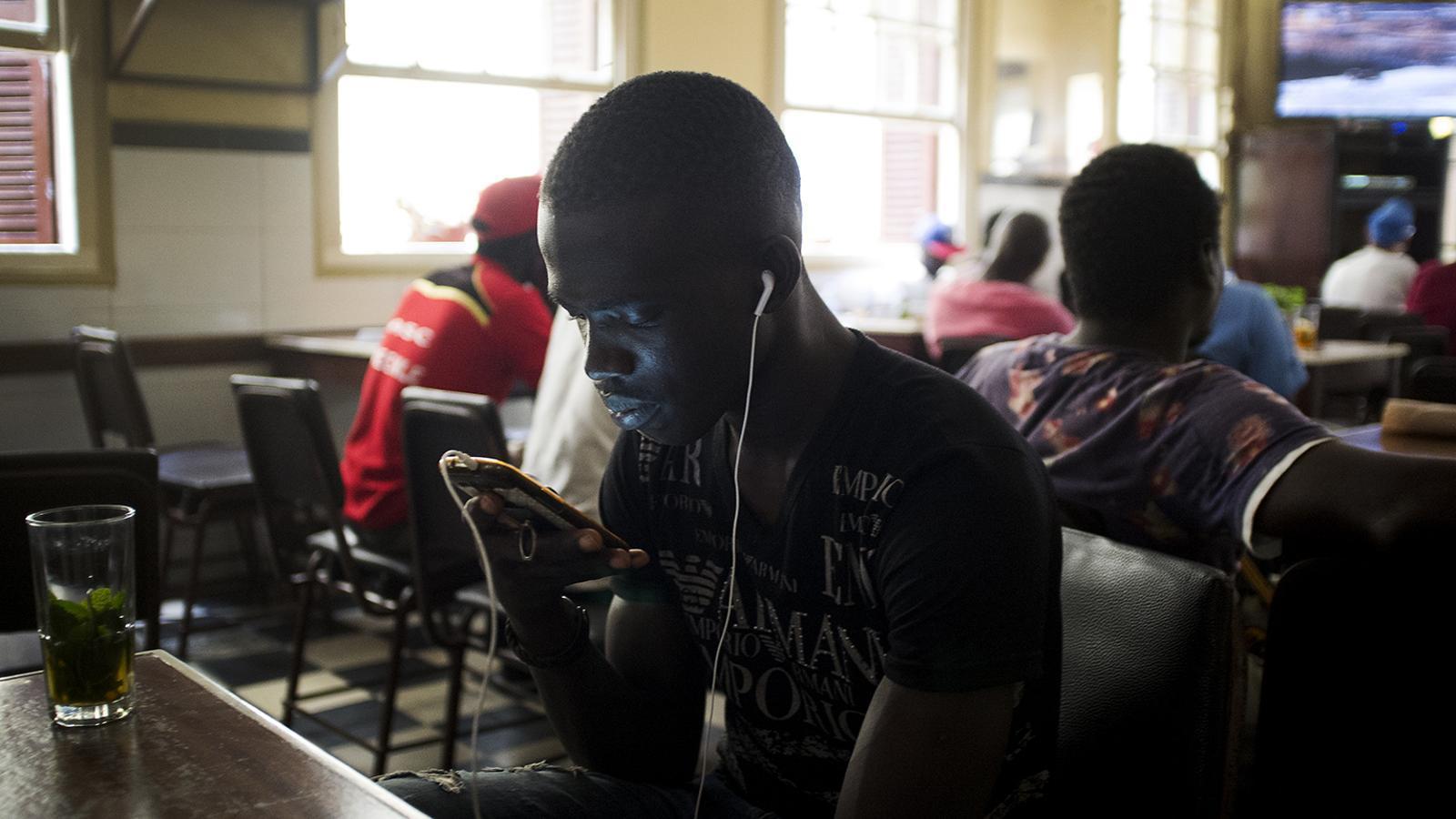 Uns homes aprofiten la connexió a internet, per contactar amb les seves famílies en un bar de la medina de Tànger