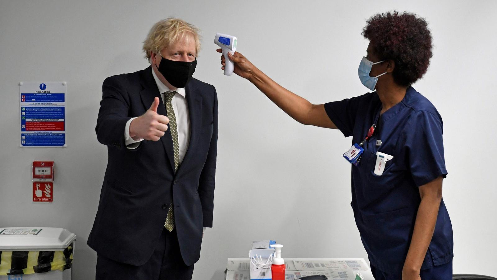 Una infermera pren la tempetarua a Boris Johnson aquest dilluns, al Chase Farm Hospital, del nord de Londres, on el primer ministre britànic ha assistit a les primeres inoculacions de ciutadans amb la vacuna d'Oxford.