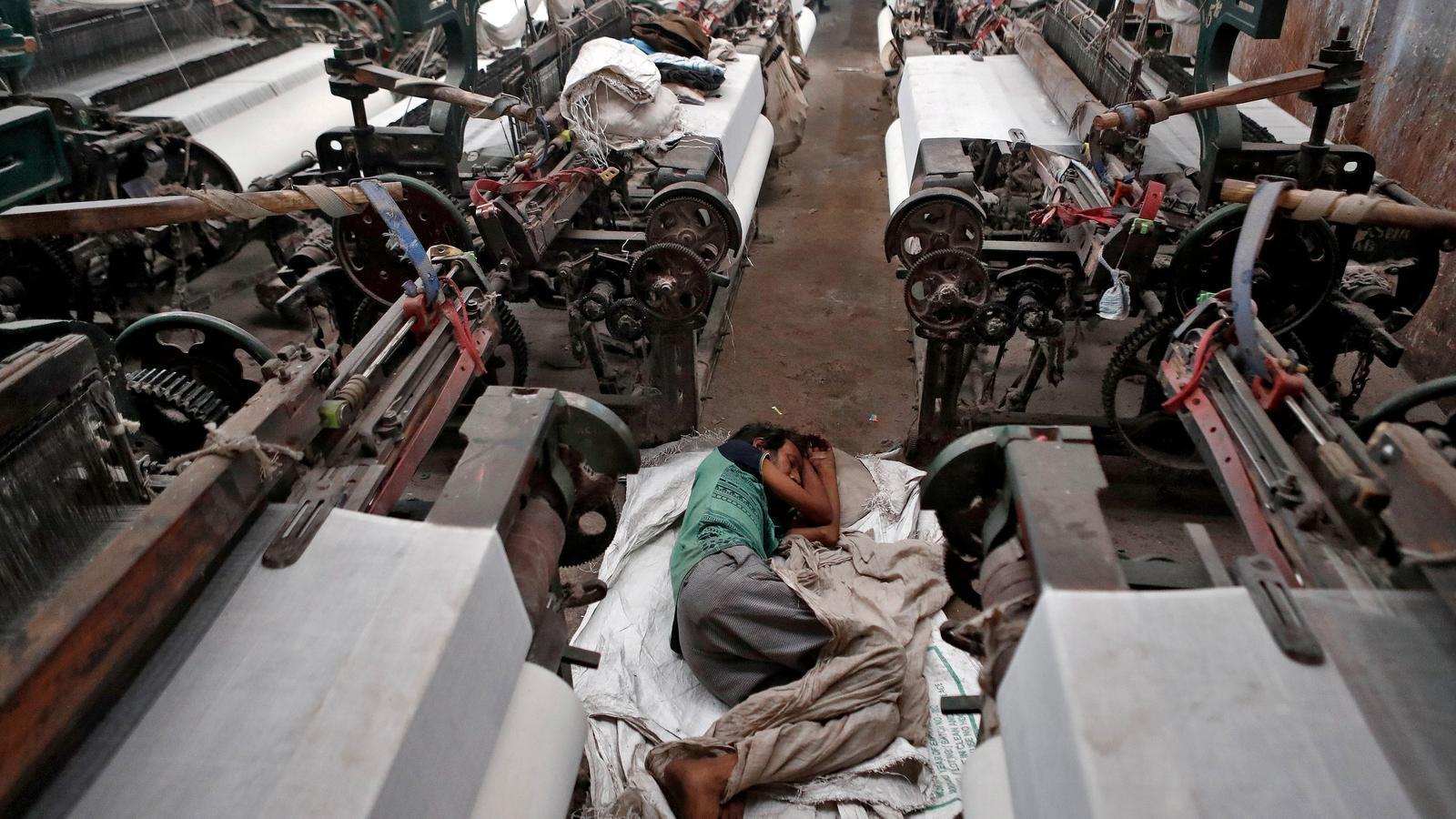 Un treballador immigrant dorm a la fàbrica tèxtil on treballava a Bombai.