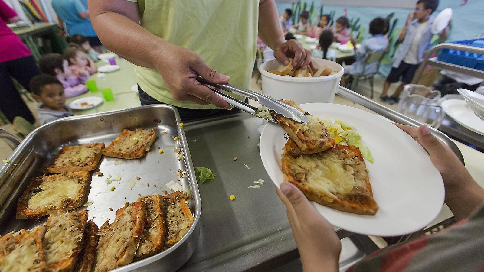 Un monitor serveix el menjar en una escola de Sant Joan Despí.