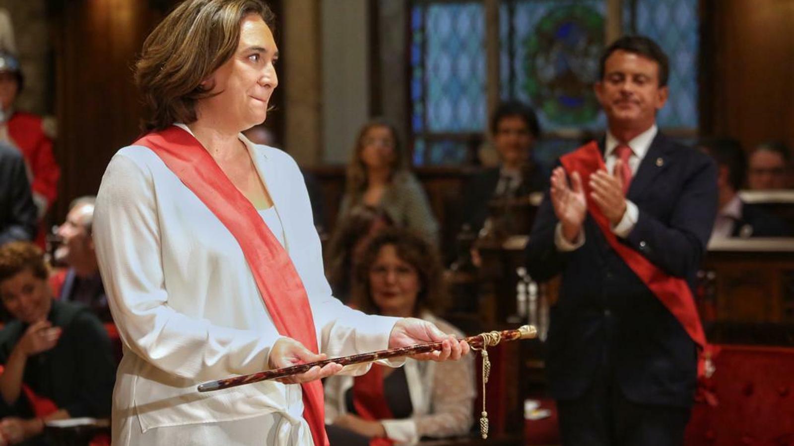 Ada Colau sosté la vara d'alcaldessa després de ser investida. Manuel Valls l'aplaudeix de fons