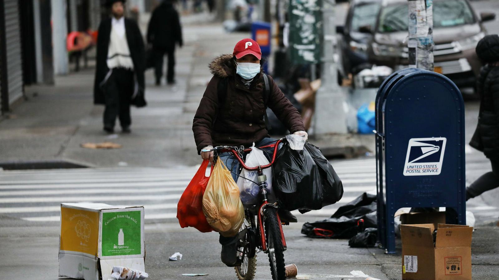 Un ciclista carregat amb bosses del supermercat al barri de Brooklyn, a Nova York.