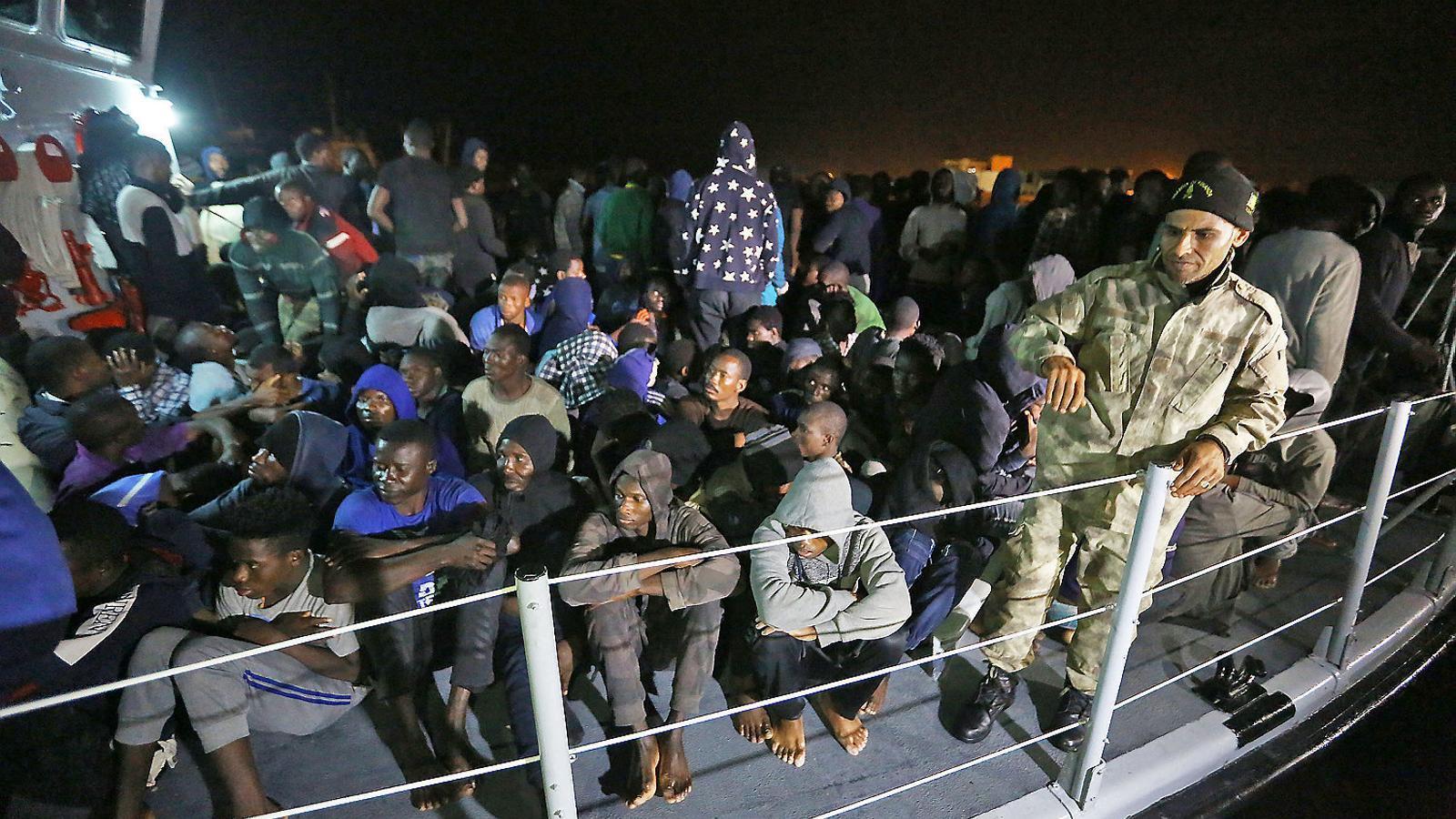 Desenes de migrants arribant a Trípoli a bord d'una patrullera de Líbia.
