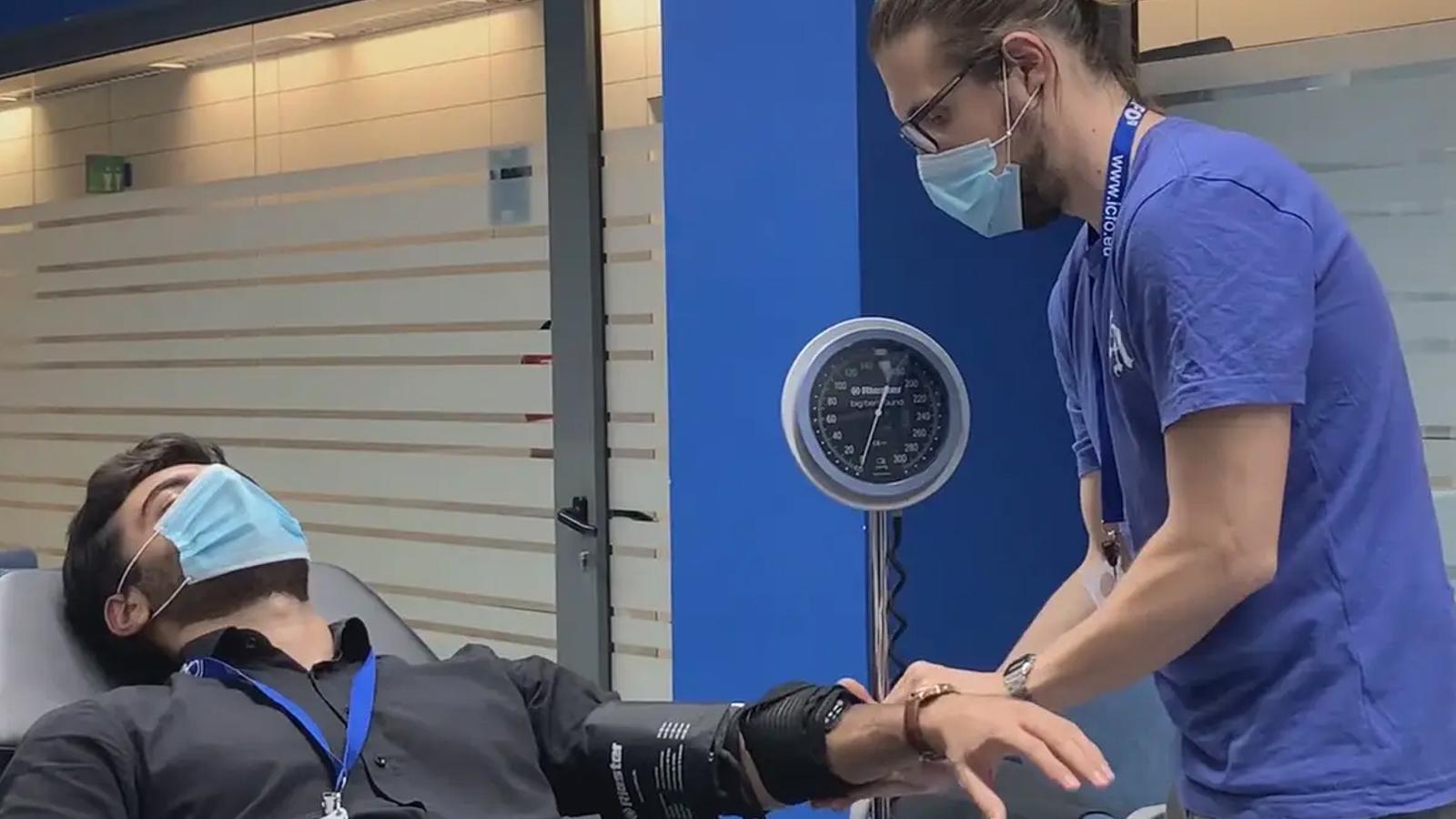 Marco Pagliazzi (de peu) i Umut Karadeniz (fent de pacient), investigadors de l'ICFO de l'equip de Turgut Durduran, fent una prova amb el dispositiu fotónic.