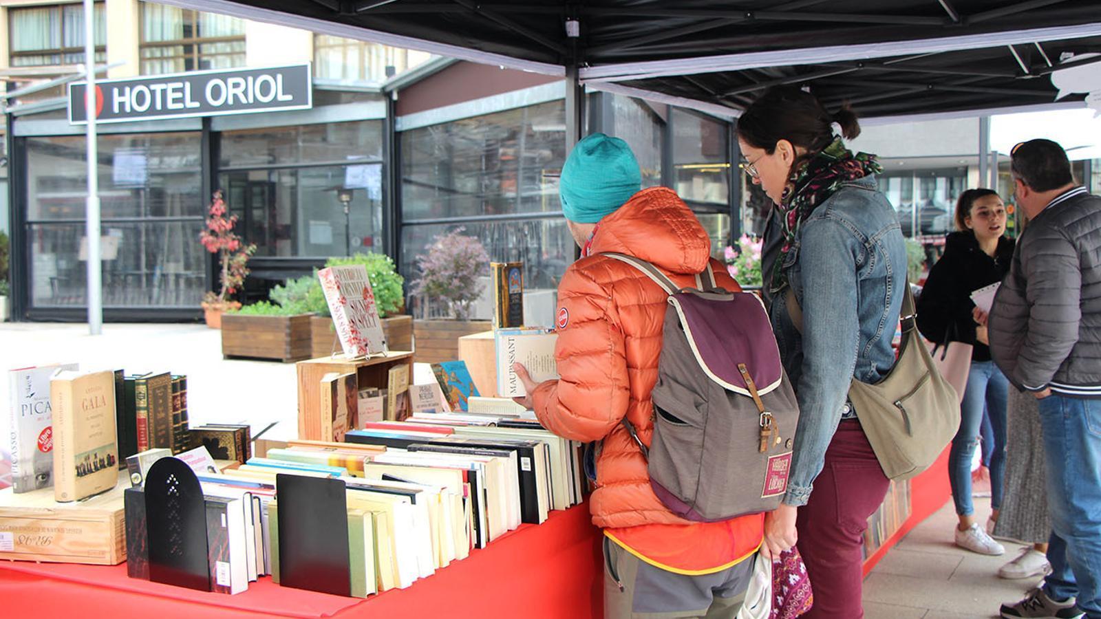 Assistents a la fira d'Escaldes-Engordany miren llibres a la parada de la biblioteca. / M. F. (ANA)