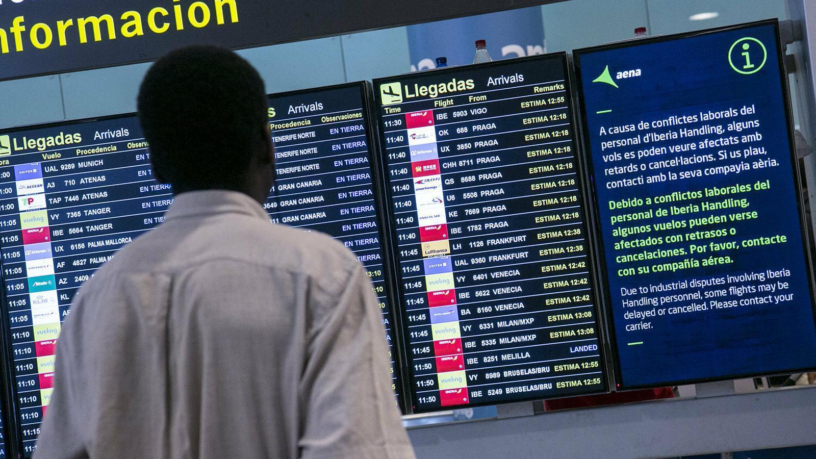 Un usuari de l'aeroport del Prat consultant l'estat dels vols en la vaga del juliol.