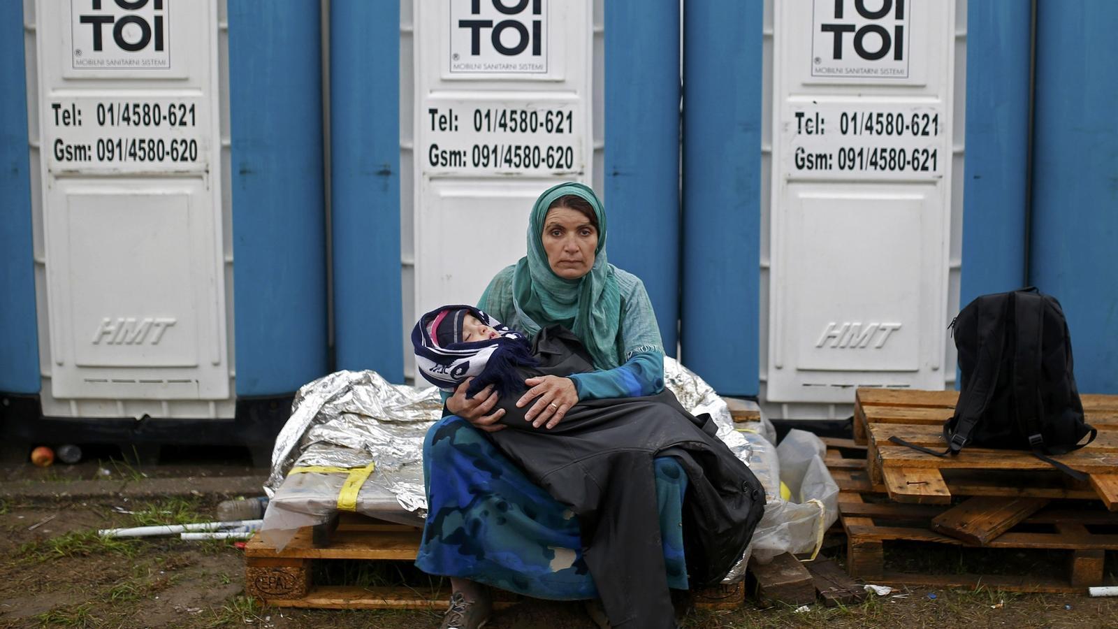 Una dona amb el seu nadó davant un lavabo portàtil a un camp de refugiats a Opatovac, Croàcia. DADO RUVIC / REUTERS