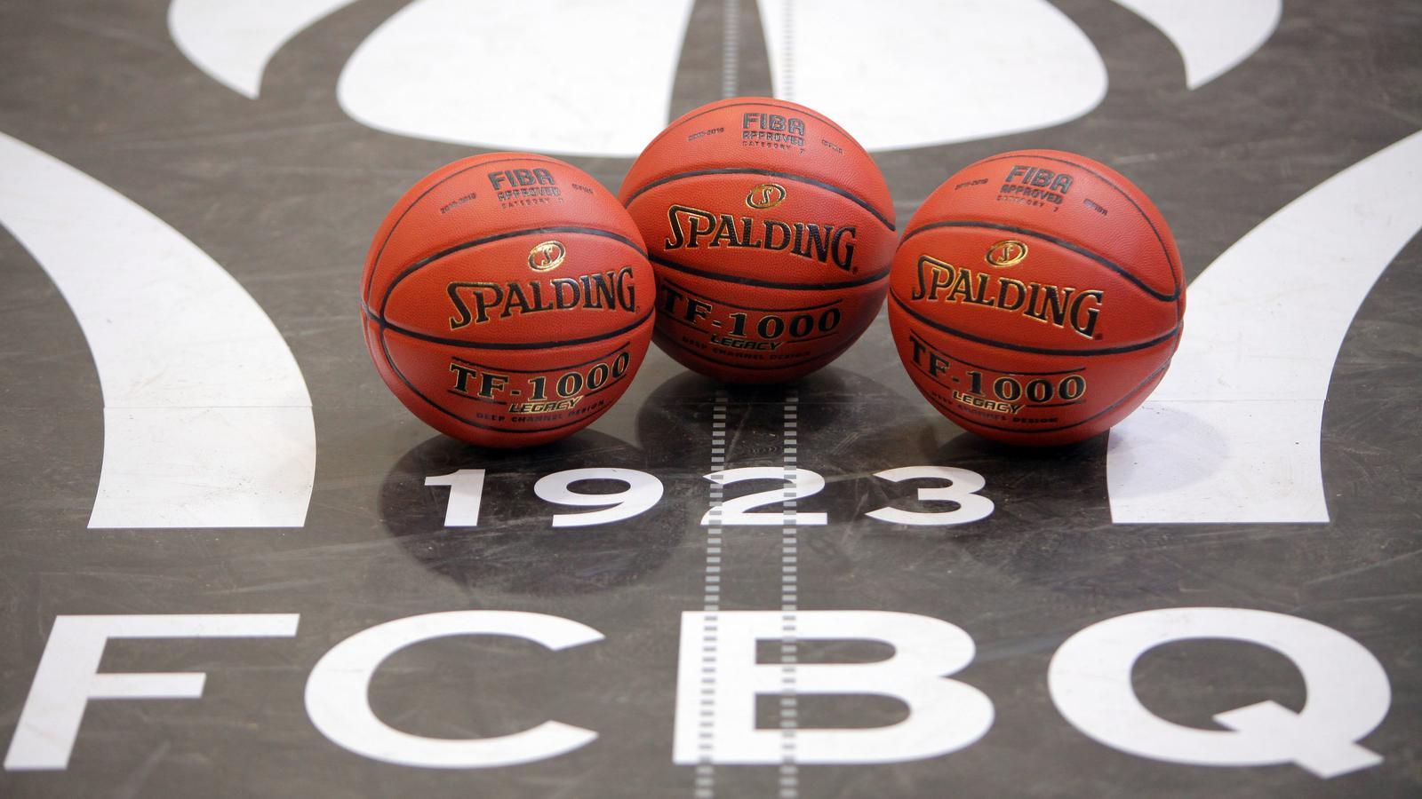 Tres pilotes de bàsquet sobre el logo de la FCBQ