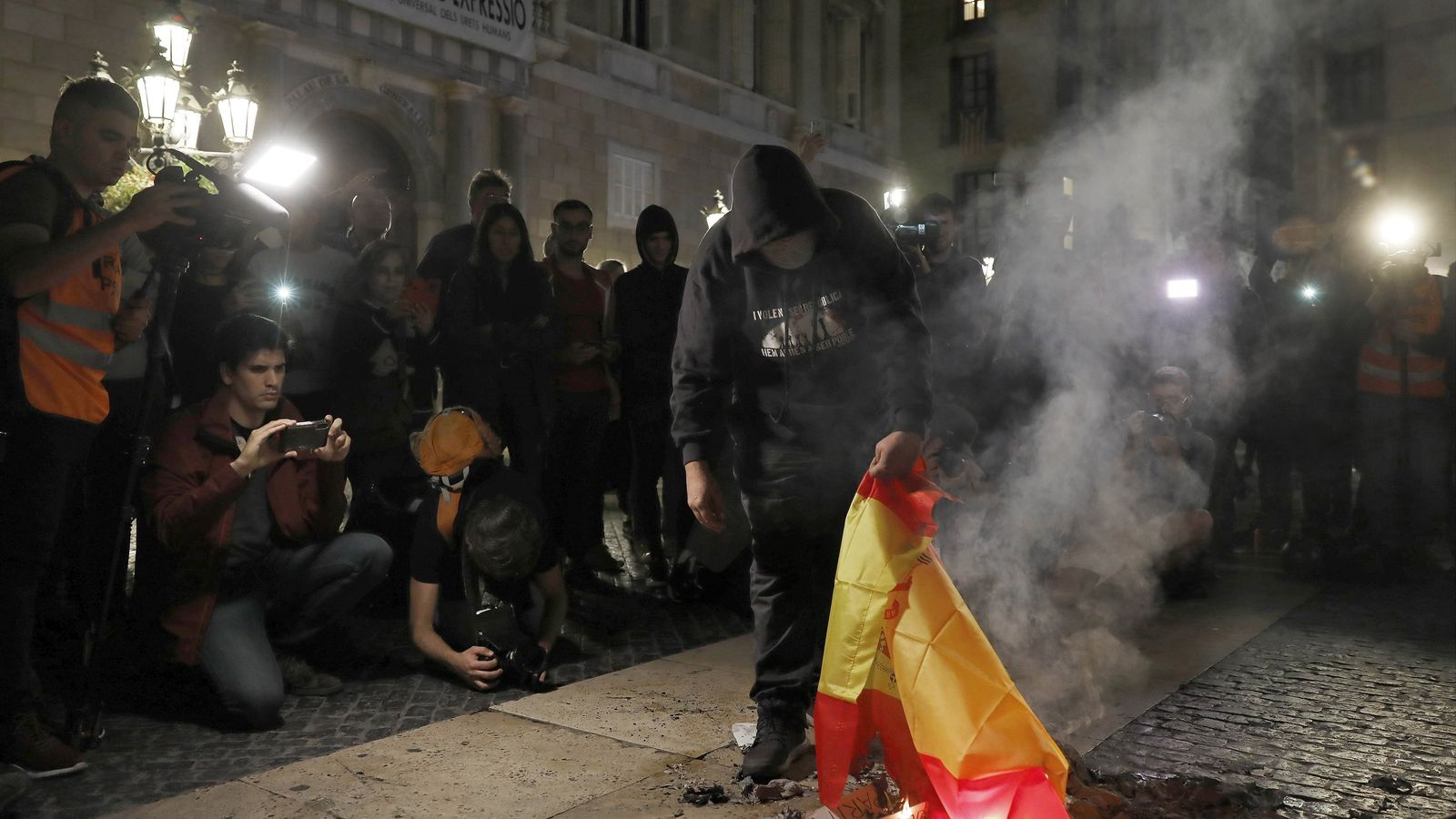 Un manifestant crema una bandera espanyola en una protesta a la plaça Sant Jaume de Barcelona / ANDREU DALMAU / EFE