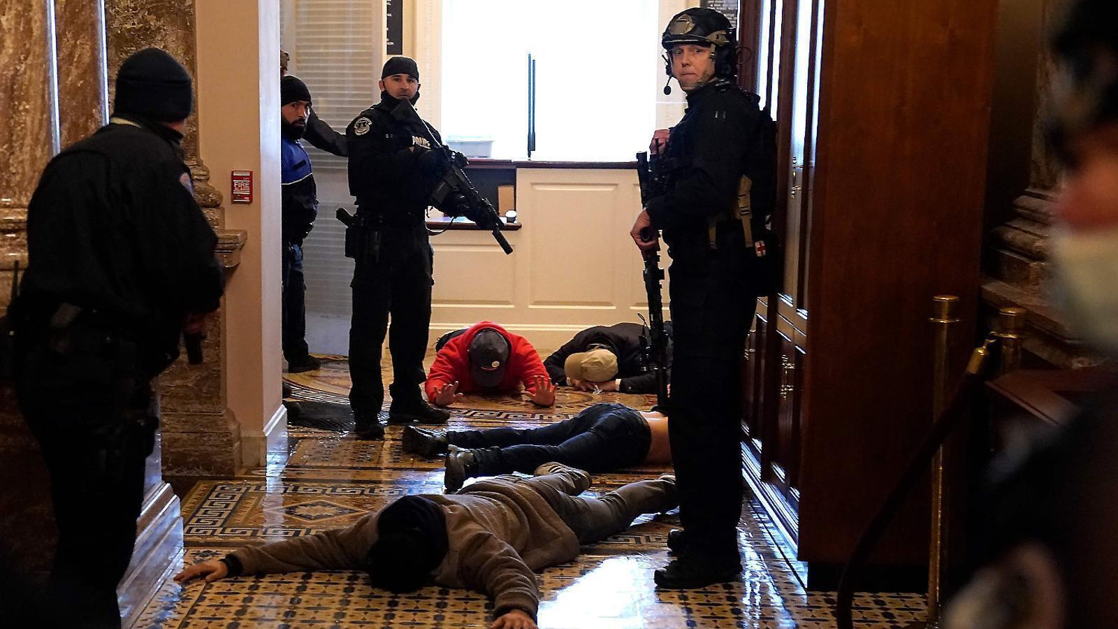 Agents de policia detenint un grup de manifestants a l'entrada de la Cambra de Representants.
