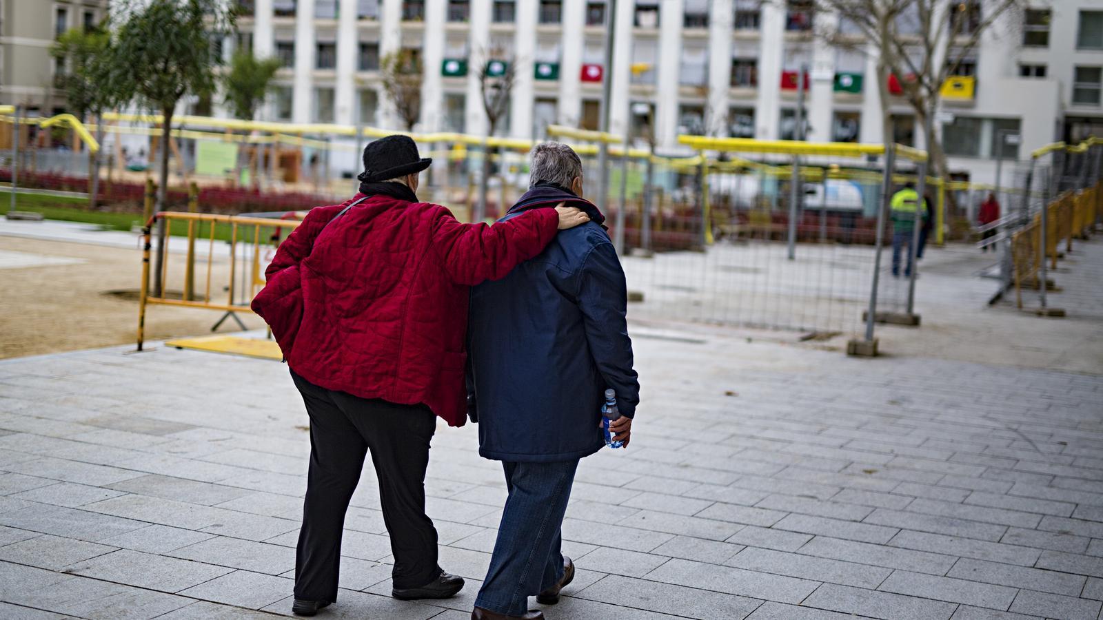 Una parella de pensionistes caminen abraçats per Barcelona