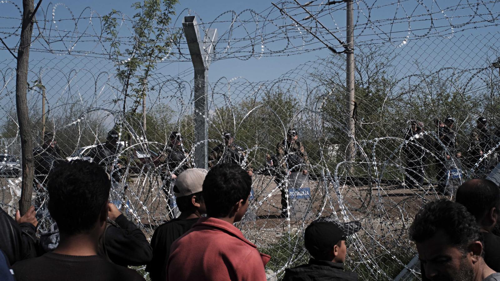 Camp de refugiats d'Idomeni, a la frontera entre Grècia i Macedònia. La policia vigila des de l'altra banda de la tanca.
