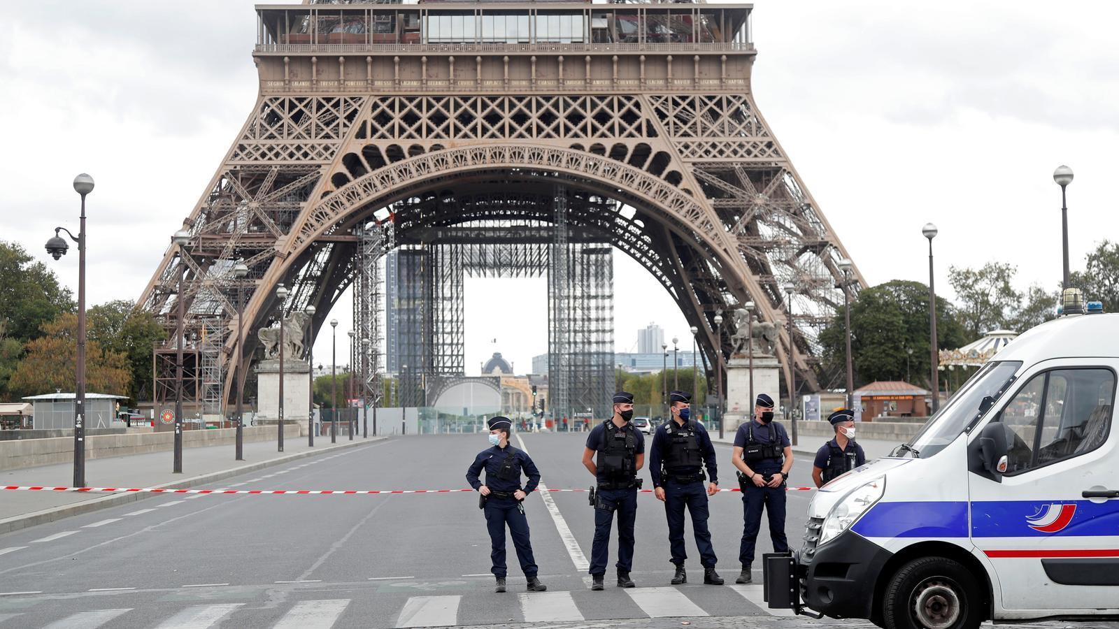 Un grup de policies francesos davant la Torre Eiffel de París, després de ser evacuada per una possible amenaça de bomba