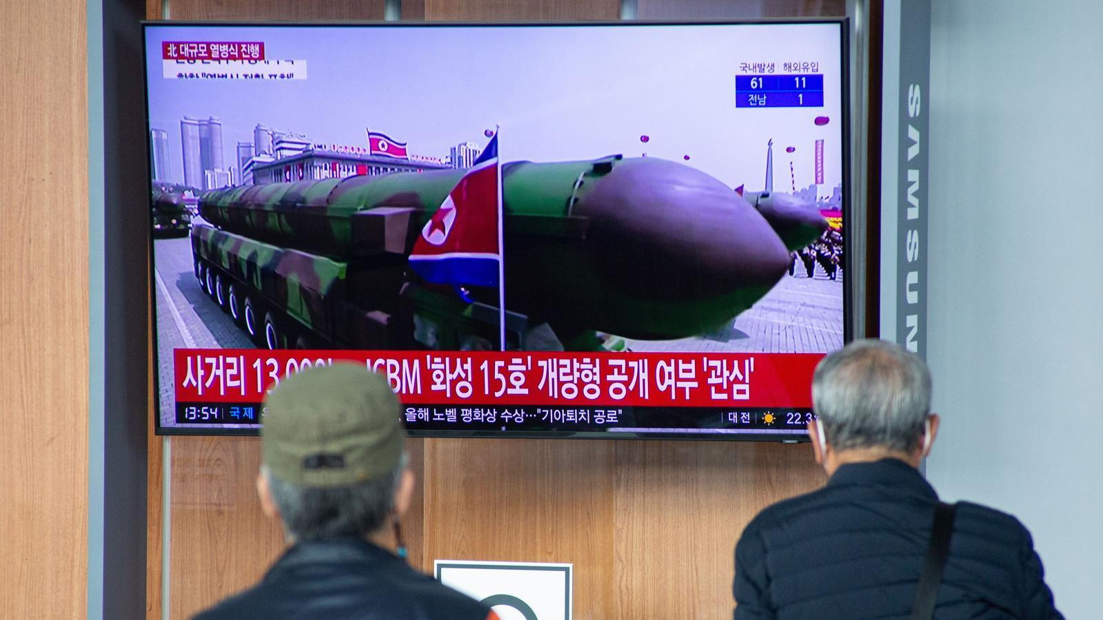 Dues persones veuen a la televisió la desfilada militar feta a Corea del Nord