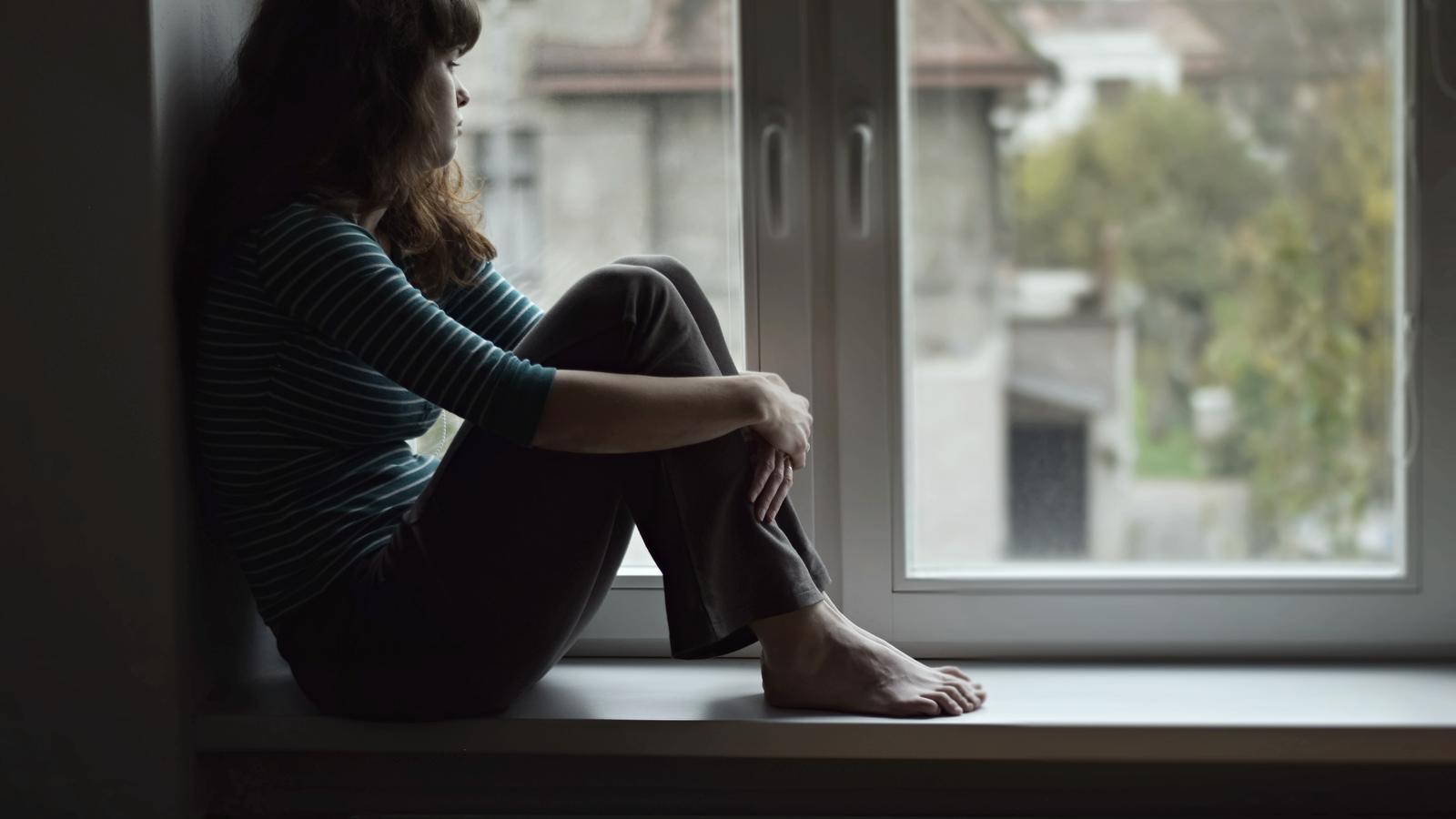 Imatge d'arxiu d'una dona que mira per la finestra
