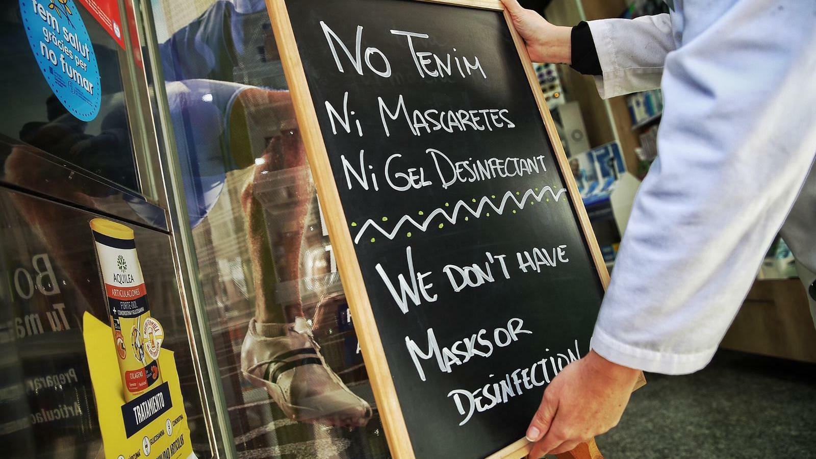 Una farmacia a l'Eixample de Barcelona col·locant un cartell advertint que no tenen mascaretes contra el coronavirus