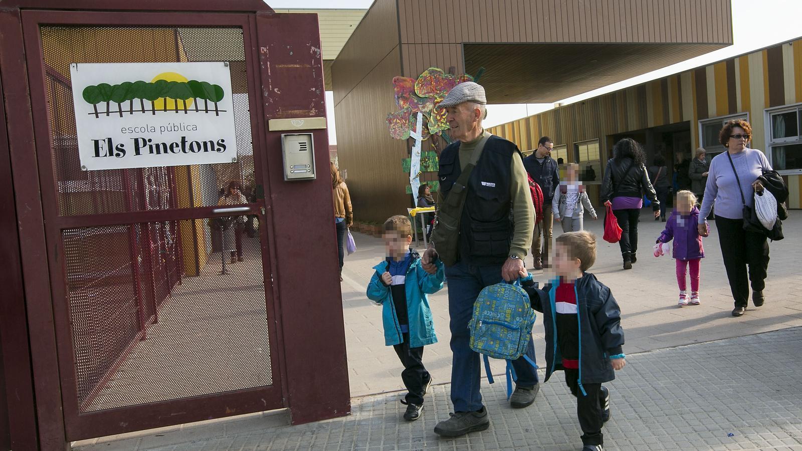 Imatge d'arxiu d'un home d'edat avançada recollint uns nens a l'escola