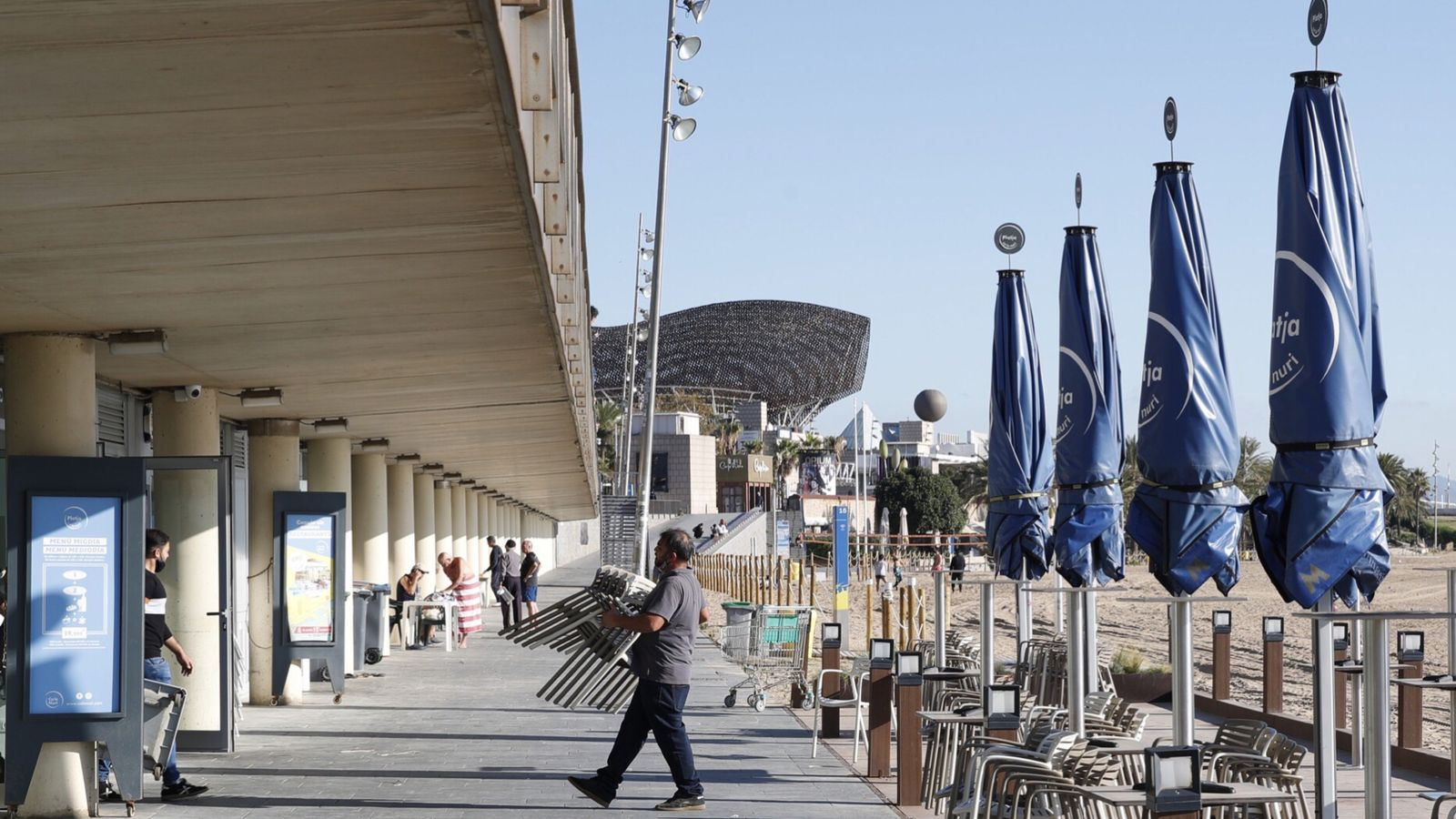 Treballadors desmuntant una terrassa a la platja de la Barceloneta